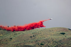 White Aircraft Dropping Fire Retardant as it Battles the Raging Wildfire Stock Photos
