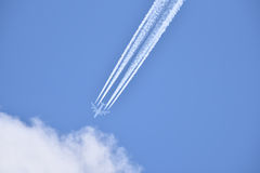 White airliner transports passengers while it pulling white contrails in blue cloudy sky Stock Photos
