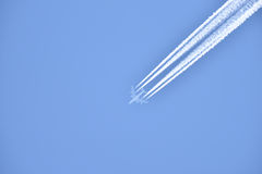 White airliner transports passengers while it pulling white contrails in blue sky Royalty Free Stock Images