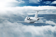 White airplane flying higher clouds at daytime Stock Image