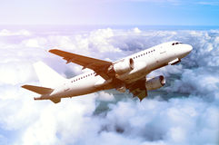 White airplane flying in the sky among white dense clouds floating over land surface. Stock Photo