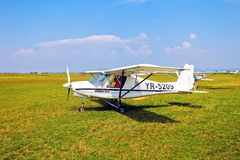 White airplane on a green grass field Stock Images
