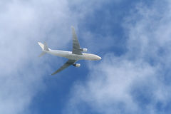 White Airplane over clouds Royalty Free Stock Photo