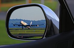 White Airplane Reflection on Car Side Mirror stock image