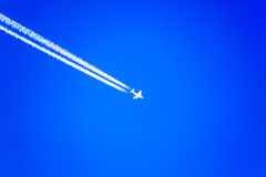 White airplane silhouette with white trail on blue sky Stock Photo