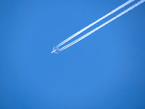 White airplane trace on blue sky Stock Image