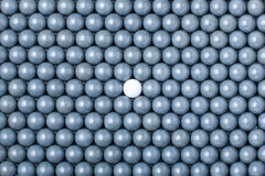White airsoft ball is among many black balls. Background of 6mm bbs Royalty Free Stock Image