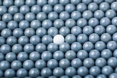 White airsoft ball is among many black balls. Background of 6mm bbs.  Royalty Free Stock Photos