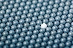 White airsoft ball is among many black balls. Background of 6mm bbs.  Royalty Free Stock Photography