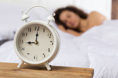 White alarm clock on the background of a sleeping girl. The girl on the bed is blurred. She lies on her right side. 9 o`clock Royalty Free Stock Image