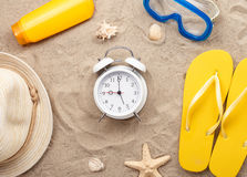White alarm clock with beach items on sand Royalty Free Stock Photography