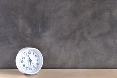 A white alarm clock on the cement wall background. A white alarm clock is placed on a wooden table and has a cement wall behind it royalty free stock photos