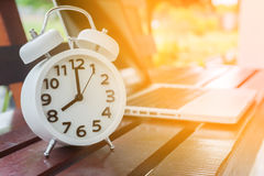 White alarm clock and laptop in morning Royalty Free Stock Photography