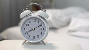 White alarm clock on night table near bed, time management, sleeping hours. Stock footage stock video