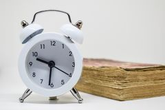White alarm clock and Old book (Dictionary) on white background stock photo