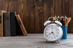 White alarm clock with old books and colored pencils Royalty Free Stock Photos