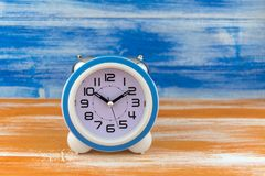 White alarm clock on a orange wooden table on blue wall background.  royalty free stock photography