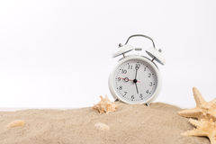 White alarm clock on the sand on a white background Stock Image