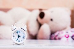 White alarm clock stands on the table on the background of a bear sleeping. In the bed royalty free stock photos