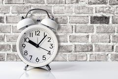 White alarm clock on table with brick wall backgroun. White alarm clock on white table with old brick wall backgroun royalty free stock photography
