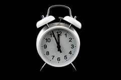 White alarmclock. Showing five for twelve isolated on black background Stock Photos