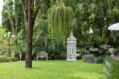 White alloy bench and giant birdcage in outdoor garden Royalty Free Stock Photography