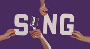 White alphabet lettering spelling SING. With the I replaced by a microphone held up over a purple studio background by outstreched female hands Stock Image