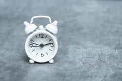 White analog alarm clock on gray background, copy space. Time theme.  royalty free stock photo