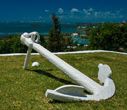 White anchor on Green Grass. An old, large, white anchor on a patch of grass overlooking a tropical sea Stock Photo