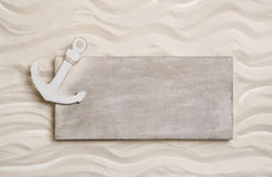 White anchor with a wooden sign in the sand. Background for crui Stock Photos