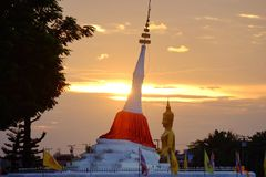 A white ancient pagoda beside a river at Kohkret,Nonthaburi sky at dusk and a large golden stock photo