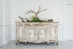 White ancient vintage commode with plants and handmade wool decoration Royalty Free Stock Photo