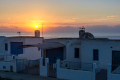 White Andalusian house. S with sea view. View of the sea with sunrise and sailboat in an Andalusian village royalty free stock images