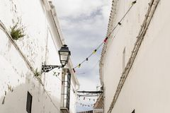 White andalusian village street with colorful lightbulbs. White andalusian village with colorful lightbulbs in summer Stock Image