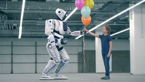 White android gives colorful balloons to a girl, side view. One cyborg gives balloons to a girl stock footage