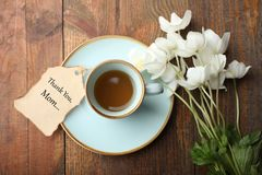 White anemone flower. Bouquet white anemone flower, cup of coffee and romantic note on wooden background. Concept mother`s day. Copy space. Top view stock images