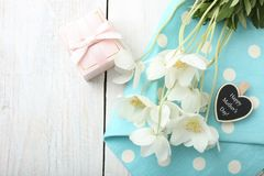 White anemone flower. Bouquet white anemone flower and gift on blue napkin on wooden background.  Concept mother`s day royalty free stock photo