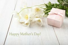 White anemone flower. Bouquet white anemone flower and gift on wooden table. Concept mother`s day. Copy space royalty free stock photography