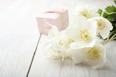 White anemone flower. Bouquet white anemone flower and gift on wooden table. Concept mother`s day. Copy space royalty free stock image