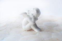 White angel. Siting an a pearl gound Royalty Free Stock Photos