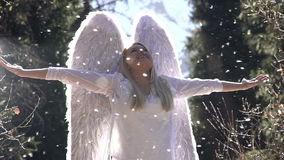 White Angel Birth. Blonde girl in a white dress with angel wings backlit sunlight. In the air, floating fluff. Motion at a rate of 240 fps stock footage