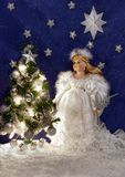 White Angel and Christmas tree. A porcelain doll in a white dress is staying near the Christmas tree. Under the tree are lying holiday gifts Royalty Free Stock Photography