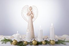 A white angel and four white Advent candles, Christmas tree branches are decorated with golden balls. The imminent Royalty Free Stock Images