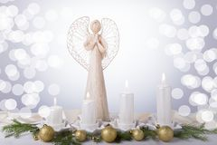 A white angel and four white Advent candles, Christmas tree branches are decorated with golden balls. The imminent Royalty Free Stock Photos