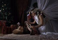 White angel and sleeping boy near Christmas tree. Woman with angel wings and sleeping boy near Christmas tree Stock Photo