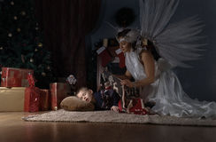White angel and sleeping boy near Christmas tree. Woman with angel wings and sleeping boy near Christmas tree Stock Images