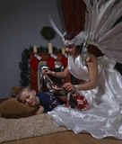 White angel and sleeping boy near Christmas tree. Woman with angel wings and sleeping boy near Christmas tree Royalty Free Stock Image