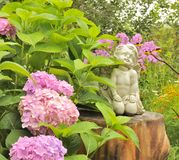 White Angel Statue on Tree Stump in the Garden. The statue of a white angel sitting on tree stump in the garden with pink hydrangea flowers Stock Image