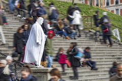 White angel. Street artist standing in the middle of in hurry and fast moving tourist on the Sacre coeur church staircase, Paris, France