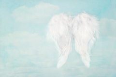 White angel wings on blue sky background. White angel wings on textured blue sky background, with copy space stock photos